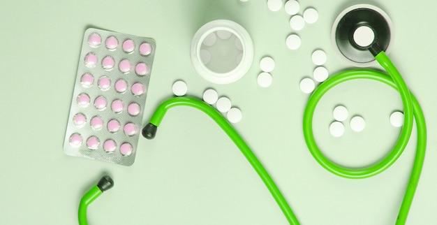 Kreatywne tło medyczne ze steoskopem i pigułki na zielonym tle. widok z góry