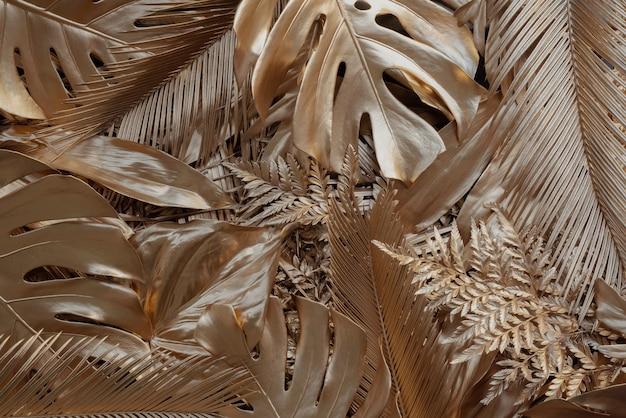 Kreatywne tło natury ze złotą tropikalną monsterą i liśćmi palmowymi minimalna letnia abstrakcja