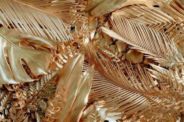 Kreatywne tło natury ze złotą tropikalną monsterą i liśćmi palmowymi minimalne letnie streszczenie dla