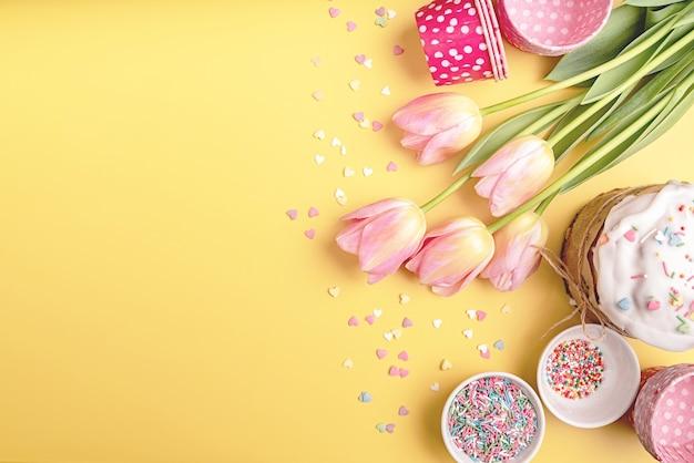 Kreatywne tło wielkanocne wakacje z ciastem wielkanocnym, tulipanami i dekoracjami widok z góry mieszkanie z miejscem na kopię