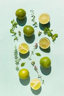 Kreatywne tło z limonki, mięty i aromatycznych ziół na pastelowym zielonym tle. koncepcja żywności. leżał na płasko.
