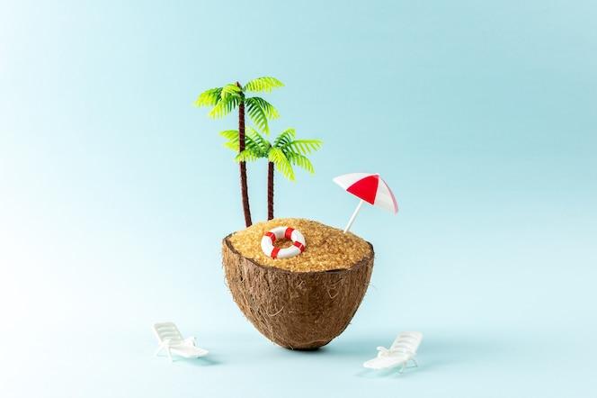 Kreatywne tło z owocami kokosowymi i palmą na pastelowym niebieskim tle