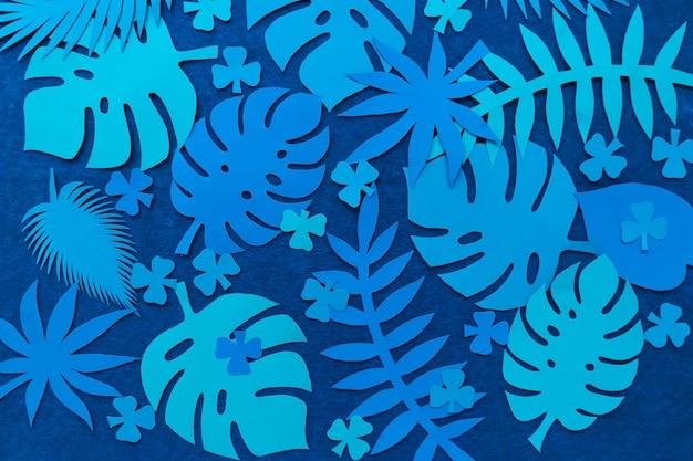 Kreatywne tropikalne liście na zielonej ścianie. widok z góry. koncepcja natury. papierowe liście tropikalne.