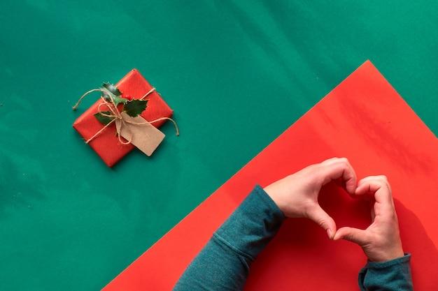 Kreatywne ukośne geometryczne mieszkanie leżało na zielonym i czerwonym papierze z długimi kwiatowymi cieniami. zapakowany prezent ozdobiony ostrokrzewem. kobiet ręki pokazuje serce znaka. ekologiczne pomysły na prezenty na boże narodzenie bez marnotrawstwa.