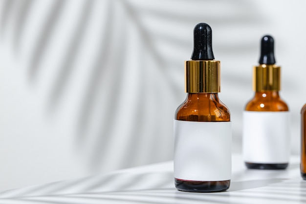 Kreatywne zdjęcie butelki kosmetycznej z pipetą na białym tle w cieniu tropikalnego kwiatu. reklama