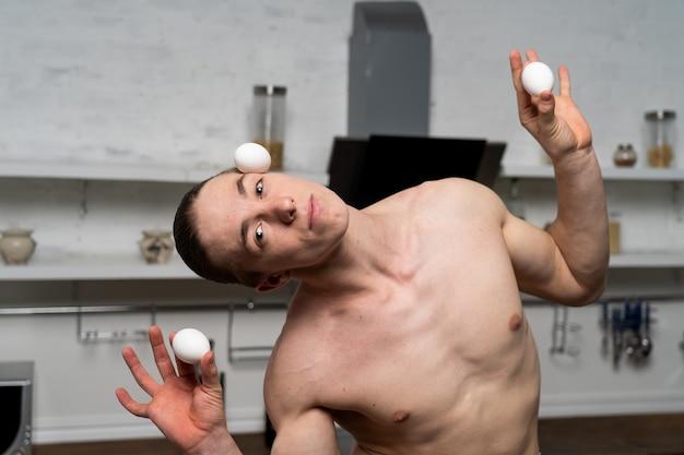 Kreatywne zdjęcie muskularnego mężczyzny w kuchni do gotowania jajek.