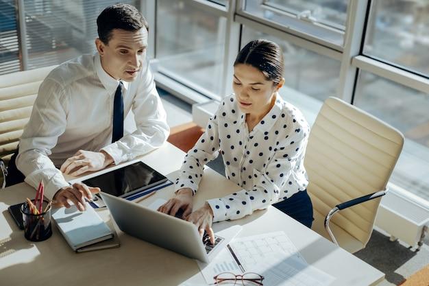Kreatywni pracownicy. widok z góry sympatycznych młodych kolegów siedzących przy stole i wspólnie rozwijających koncepcję wspólnego nowego projektu