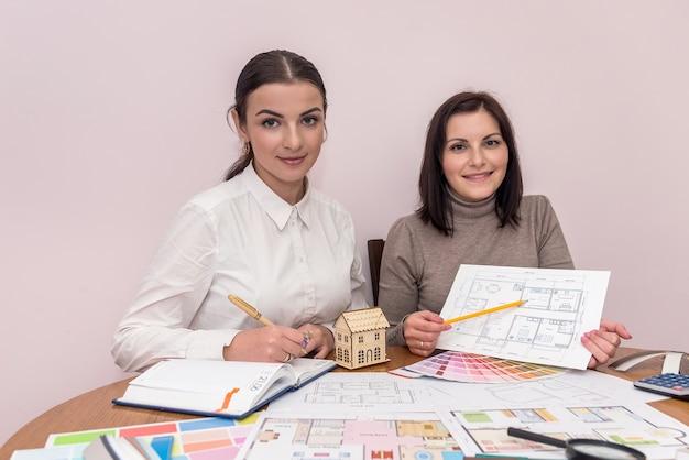 Kreatywni projektanci przedstawiający projekt domu i pozujący