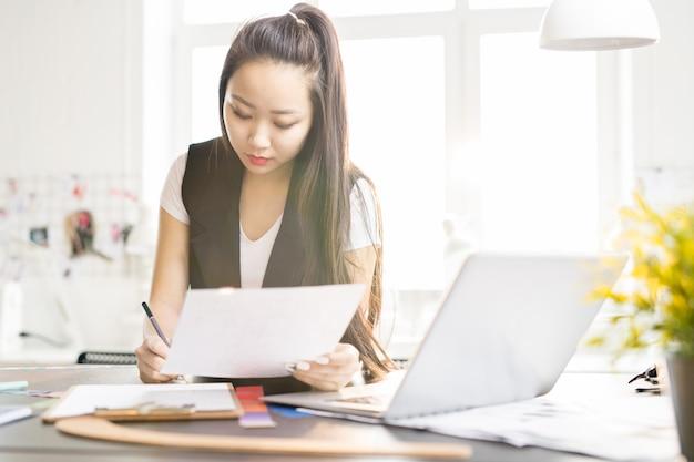 Kreatywnie azjatycka kobieta pracuje w studio projektowym