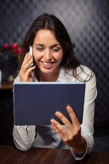 Kreatywnie bizneswoman używa pastylkę i smartphone