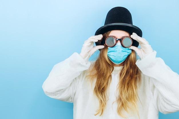 Kreatywnie dziewczyna w białej szacie, masce medycznej, okularach i kapeluszu na niebieskim tle. samoizolacja podczas kwarantanny koronawirusa. epidemic covid-2019.