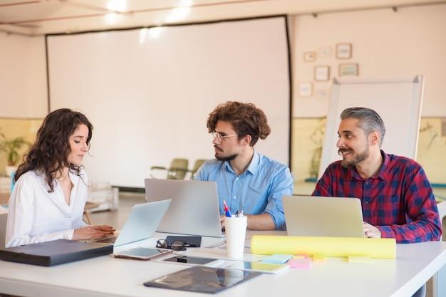 Kreatywnie grupa dyskutuje pomysły w sala posiedzeń z laptopami