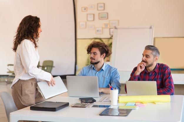 Kreatywnie grupa z laptopami zbiera w pokoju konferencyjnym