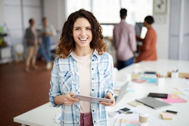 Kreatywnie kobieta ono uśmiecha się w biurze