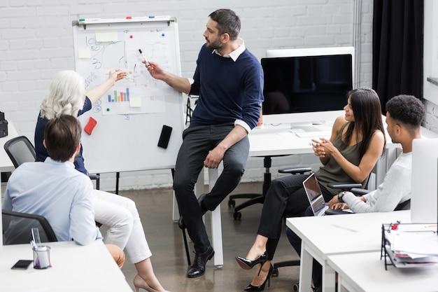 Kreatywnie ludzie siedzi przy stołem w sala posiedzeń