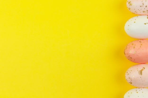Kreatywnie malowane jajka w pastelowych kolorach ozdobione złotym liściem ułożone są w rzędzie wzdłuż bocznej krawędzi na żółtym tle, kopia przestrzeń. szczęśliwa wielkanocna koncepcja diy. leżał płasko. poziomy