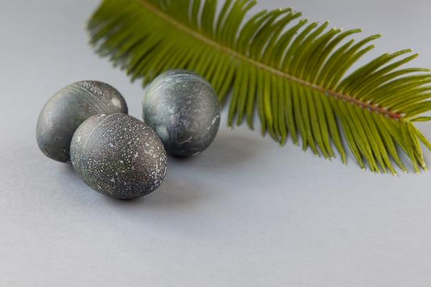 Kreatywnie malowane jajka wielkanocne z kurczaka z naturalnym barwnikiem hibiskusa, wyglądają jak kamienie morskie, liść palmy daktylowej na szarej powierzchni,