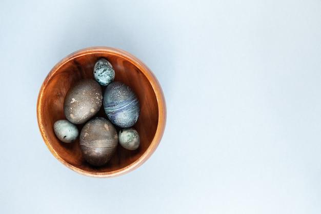 Kreatywnie malowane jajko wielkanocne z kurczaka i przepiórki na drewnianej misce