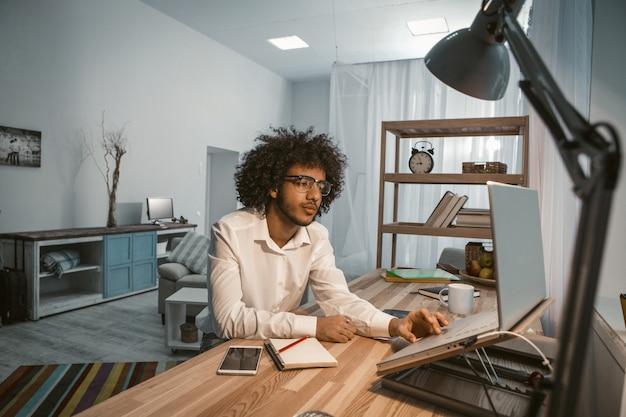 Kreatywnie mężczyzna pracuje laptopu domowego biura wnętrze. miejsce pracy copywriter lub projektant. pojęcie nadgodzin. koncepcja niezależna. barwiony obraz