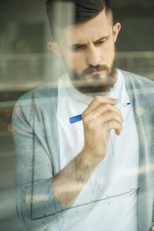 Kreatywnie mężczyzna rysunkowa strategia biznesowa przy biurowym okno.