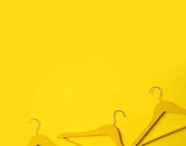 Kreatywnie mieszkanie kłaść drewniani wieszaki przy koloru żółtego stołem z kopii przestrzenią.