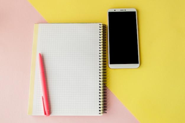 Kreatywnie mieszkanie nieatutowa fotografia biurka obszaru roboczego z smartphone i notatnika z kopii przestrzeni tłem, minimalny styl