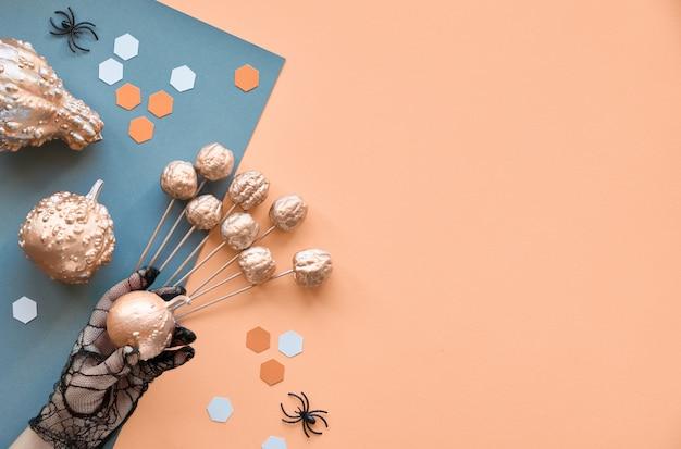 Kreatywnie papierowego rzemiosła halloween tło. mieszkanie leżało z pająkami, dynią w ręku i sześciokątami na tle podzielonego papieru w lorange i szarości z kopią