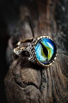 Kreatywnie pierścionek z smoka okiem na drewnianym tle