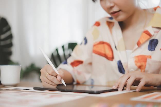 Kreatywnie projektant grafik komputerowych używa cyfrowego pióra rysunek na pastylce podczas gdy pracujący w domu biuro.
