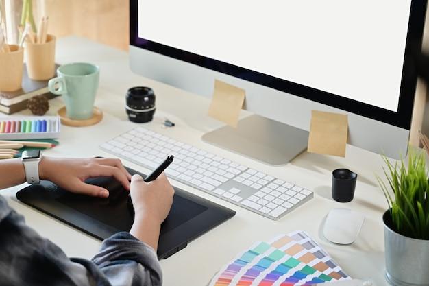 Kreatywnie projektant używa cyfrową rysunkową pastylkę w pracownianym miejscu pracy
