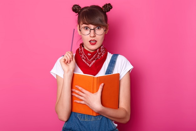 Kreatywnie śliczna uczennica stoi odizolowana nad różową ścianą w studio, szeroko otwiera usta i oczy, trzymając pióro w jednej ręce i pomarańczowy notatnik w drugiej, mając nowy pomysł. koncepcja edukacji.