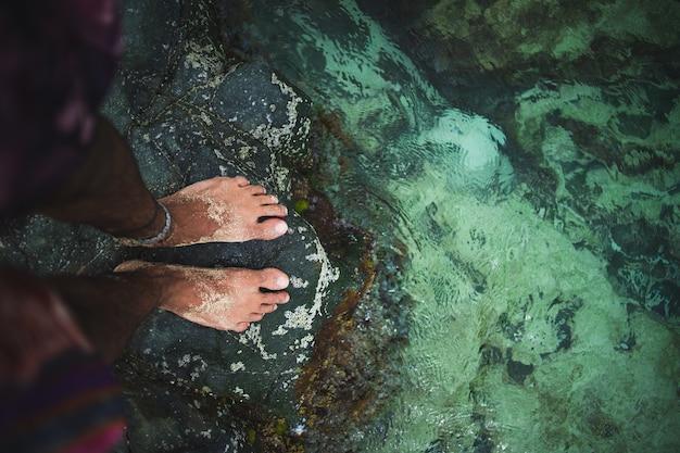 Kreatywnie strzał samiec z jego stopami w wodzie w st maarten, karaiby