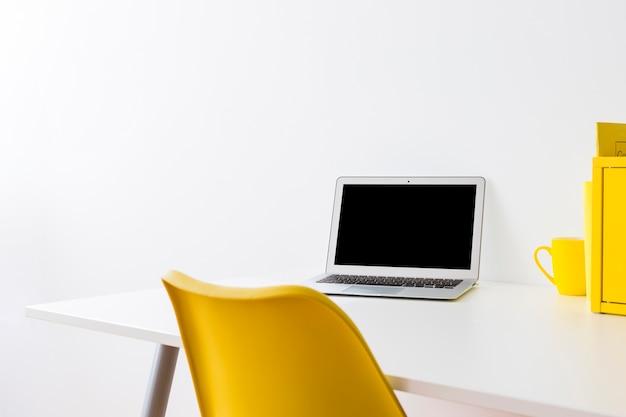 Kreatywnie workspace z żółtym krzesłem i pudełkiem