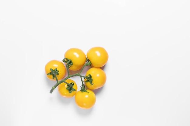 Kreatywnie żółci pomidory na białym odosobnionym tle