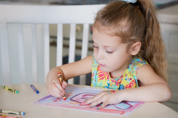 Kreatywność dla dzieci. małe dziecko dziewczyna rysuje w domu ołówkami woskowymi. koncepcja kształcenia na odległość online na okres globalnej kwarantanny.