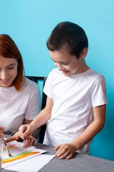 Kreatywność dzieci. chłopiec maluje farbą na niebieskim tle, widok z góry