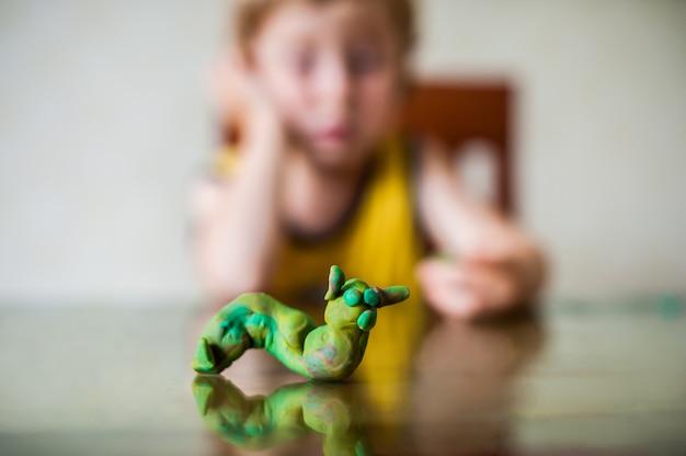 Kreatywność dzieci. dziecko rzeźbi z gliny. śliczny chłopiec formuje z plasteliny na stole