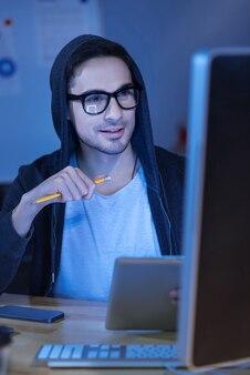 Kreatywność i innowacja. przyjemny inteligentny przystojny mężczyzna trzymający ołówek i korzystający z tabletu, mając jednocześnie kilka nowych pomysłów na swój projekt