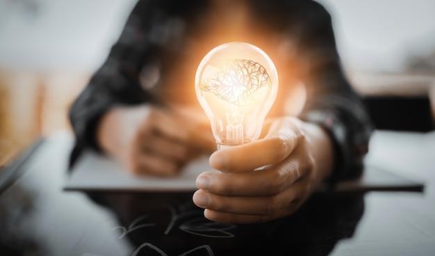 Kreatywność i innowacyjność to klucze do sukcesu. koncepcja nowego pomysłu i innowacji z brain i żarówkami.