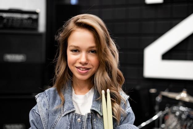 Kreatywność i muzyka. młoda piękna dziewczyna gra na perkusji. twarz z bliska. pałeczki. studio nagrań. sprzęt muzyczny.