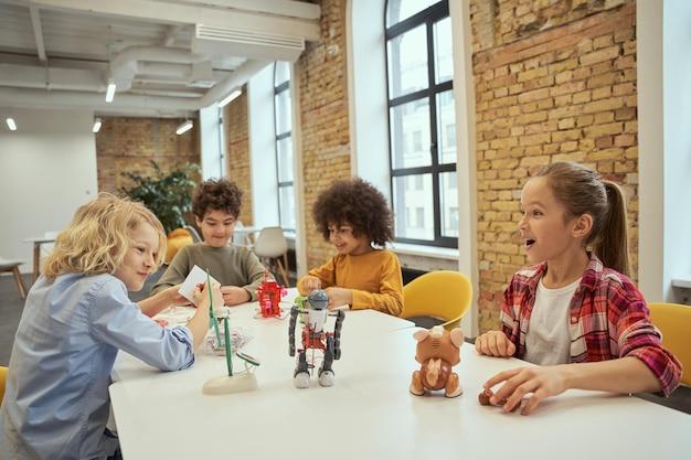 Kreatywność żywe, różnorodne dzieci wyglądające na podekscytowane podczas zabawy zabawkami technicznymi spędzającymi czas w