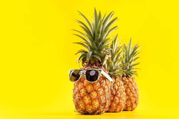 Kreatywny ananas patrząc w górę z okularami przeciwsłonecznymi i muszlą na białym tle na żółtym tle, kopia przestrzeń z bliska
