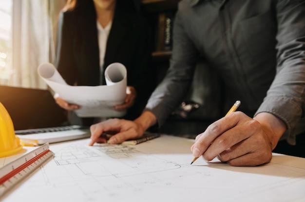 Kreatywny architekt projektujący duże rysunki w ciemnym biurze na poddaszu lub kawiarni w porannym świetle