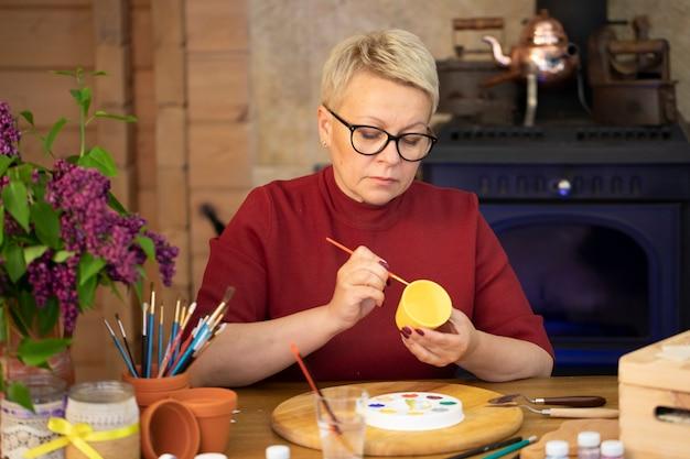 Kreatywny artysta maluje na glinianym garnku ceramicznym w obszarze roboczym pracowni domowej sztuki