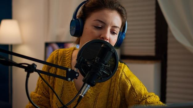 Kreatywny bloger w słuchawkach sprawdzający dźwięk przed rozmową z fanami podczas transmisji na żywo w mediach społecznościowych, podcastów. internetowa transmisja internetowa na żywo, która jest gospodarzem transmisji strumieniowej treści na żywo