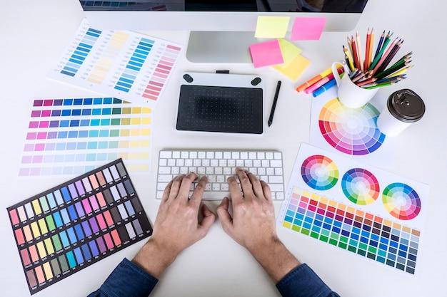 Kreatywny grafik pracujący nad wyborem kolorów i rysowaniem na tablecie graficznym w miejscu pracy