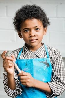 Kreatywny i uroczy uczeń w niebieskim fartuchu trzymając pędzel stojąc w izolacji w studio