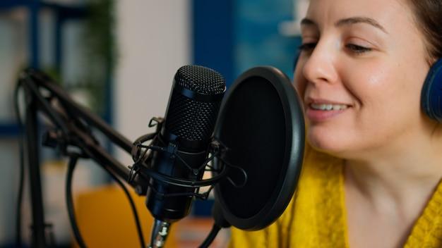 Kreatywny influencer ze słuchawkami mówiącymi podczas transmisji na żywo, bloger dyskutujący w podcastach w mediach społecznościowych. internetowa transmisja internetowa na żywo, która jest gospodarzem transmisji strumieniowej treści na żywo