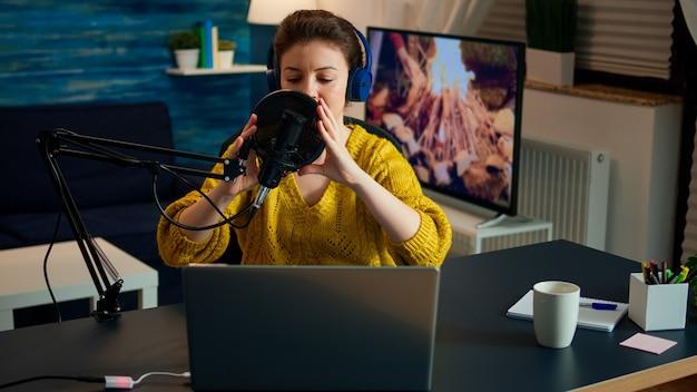 Kreatywny influencer ze słuchawkami przygotowujący się do przemawiania na żywo w mediach społecznościowych nagrywający wideo vlog. internetowa transmisja internetowa na żywo z produkcji online, hostująca zawartość podcastów strumieniowych ze studia