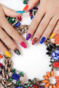 Kreatywny jasny nasycony manicure na długich paznokciach z kryształkami.